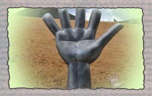 Скульптура ладони на фоне поля,вместе с детской ладонью